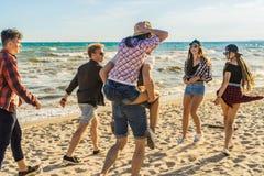 Groupe de jeunes amis de hippie courant le long de la plage ensemble Image stock