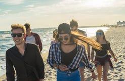 Groupe de jeunes amis de hippie courant le long de la plage ensemble Images stock
