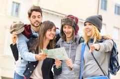 Groupe de jeunes amis de touristes de hippie encourageant avec la carte de ville Images libres de droits