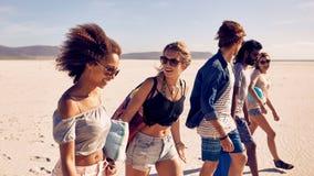 Groupe de jeunes amis descendant une plage Images libres de droits