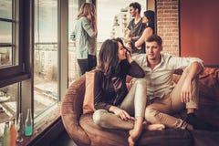 Groupe de jeunes amis ethniques multi ayant l'amusement dans l'intérieur à la maison Photo stock