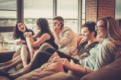 Groupe de jeunes amis ethniques multi ayant l'amusement dans l'intérieur à la maison Photographie stock libre de droits