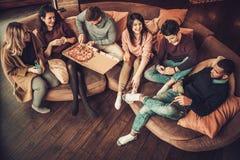 Groupe de jeunes amis ethniques multi mangeant de la pizza dans l'intérieur à la maison Image stock
