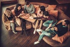 Groupe de jeunes amis ethniques multi mangeant de la pizza dans l'intérieur à la maison Images libres de droits