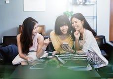 Groupe de jeunes amis féminins asiatiques dans le café, utilisant les dispositifs numériques, causant Photos libres de droits