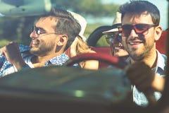 Groupe de jeunes amis gais conduisant la voiture et souriant en été Image libre de droits