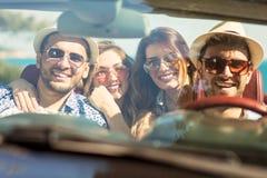 Groupe de jeunes amis gais conduisant la voiture et souriant en été Images stock