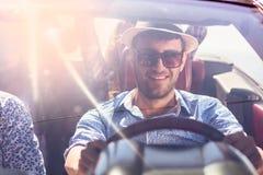 Groupe de jeunes amis gais conduisant la voiture et souriant en été Photo libre de droits