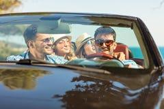 Groupe de jeunes amis gais conduisant la voiture et souriant en été Photo stock