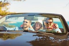 Groupe de jeunes amis gais conduisant la voiture et souriant en été Photos libres de droits