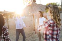 Groupe de jeunes amis gais jouant avec la boule Photos stock
