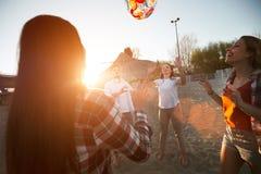 Groupe de jeunes amis gais jouant avec la boule Photographie stock libre de droits