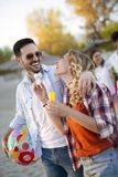 Groupe de jeunes amis gais jouant avec la boule Image stock