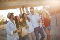 Groupe de jeunes amis gais marchant et buvant de la bière Image stock