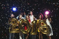 Groupe de jeunes amis heureux avec des ballons de nombre à la partie de nouvelle année Photographie stock libre de droits