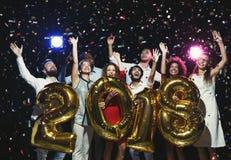 Groupe de jeunes amis heureux avec des ballons de nombre à la partie de nouvelle année Photographie stock