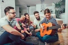 Groupe de jeunes amis heureux avec la guitare ayant l'amusement Image stock
