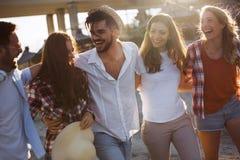 Groupe de jeunes amis heureux ayant le grand temps sur la plage Image libre de droits