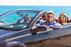 Groupe de jeunes amis heureux dans le cabriolet avec les mains augmentées conduisant sur le coucher du soleil Image libre de droits