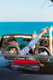 Groupe de jeunes amis heureux dans le cabriolet avec les mains augmentées conduisant sur le coucher du soleil Images libres de droits
