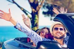 Groupe de jeunes amis heureux dans le cabriolet avec les mains augmentées conduisant sur le coucher du soleil Photo stock