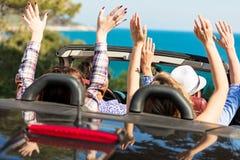 Groupe de jeunes amis heureux dans le cabriolet avec les mains augmentées conduisant sur le coucher du soleil Photos stock