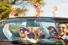 Groupe de jeunes amis heureux dans le cabriolet avec les mains augmentées conduisant sur le coucher du soleil Photos libres de droits