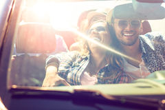 Groupe de jeunes amis heureux dans le cabriolet avec les mains augmentées conduisant sur le coucher du soleil Image stock