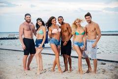 Groupe de jeunes amis heureux gais se tenant à la plage Images libres de droits