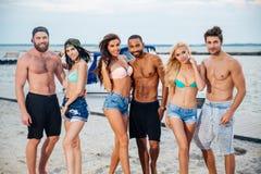 Groupe de jeunes amis heureux gais se tenant à la plage Photo stock