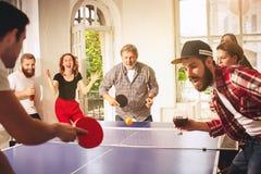 Groupe de jeunes amis heureux jouant le ping-pong de ping-pong Image stock