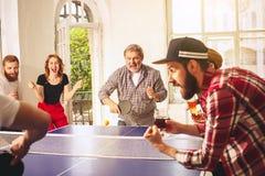 Groupe de jeunes amis heureux jouant le ping-pong de ping-pong Photographie stock