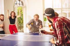 Groupe de jeunes amis heureux jouant le ping-pong de ping-pong Photo stock