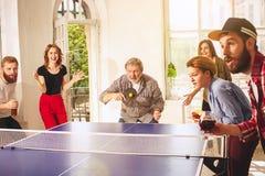 Groupe de jeunes amis heureux jouant le ping-pong de ping-pong Photographie stock libre de droits