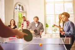 Groupe de jeunes amis heureux jouant le ping-pong de ping-pong Photos libres de droits