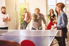 Groupe de jeunes amis heureux jouant le ping-pong de ping-pong Images stock