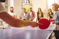 Groupe de jeunes amis heureux jouant le ping-pong de ping-pong Photos stock