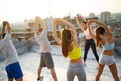 Groupe de jeunes amis heureux de personnes s'exer?ant dehors au coucher du soleil images stock