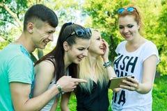 Groupe de jeunes amis heureux regardant le téléphone portable Photo stock