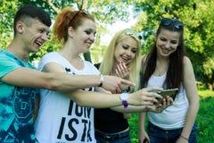 Groupe de jeunes amis heureux regardant le téléphone portable Photographie stock