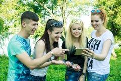 Groupe de jeunes amis heureux regardant le téléphone portable Image stock