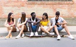 Groupe de jeunes amis de hippie parlant dans une zone urbaine Photos stock