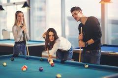 Groupe de jeunes amis jouant le billard Photographie stock libre de droits