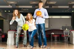 Groupe de jeunes amis jouant le bowling Photo stock