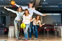 Groupe de jeunes amis jouant le bowling Photographie stock libre de droits