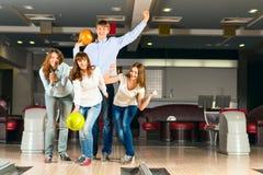 Groupe de jeunes amis jouant le bowling Image libre de droits