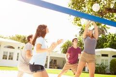 Groupe de jeunes amis jouant le match de volleyball Image stock
