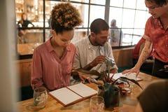 Groupe de jeunes amis lisant des menus à une table de restaurant Photographie stock libre de droits