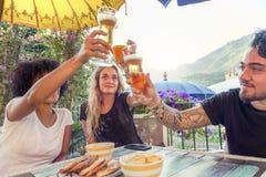 Groupe de jeunes amis mangeant des casse-croûte et le boire Images stock
