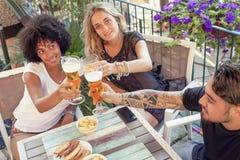 Groupe de jeunes amis mangeant des casse-croûte et le boire Image stock